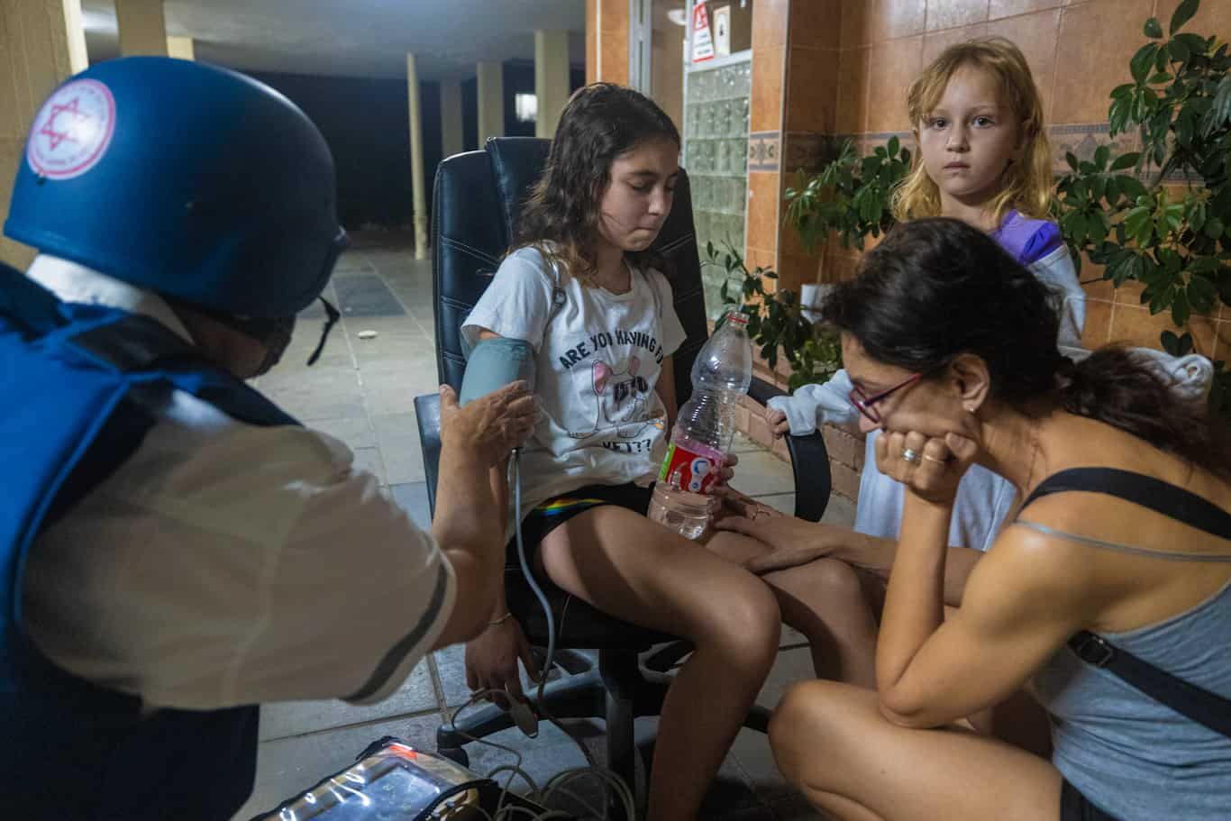A paramedic checks the blood pressure of a young Israeli girl after her building was hit by a rocket in Ashkelon
