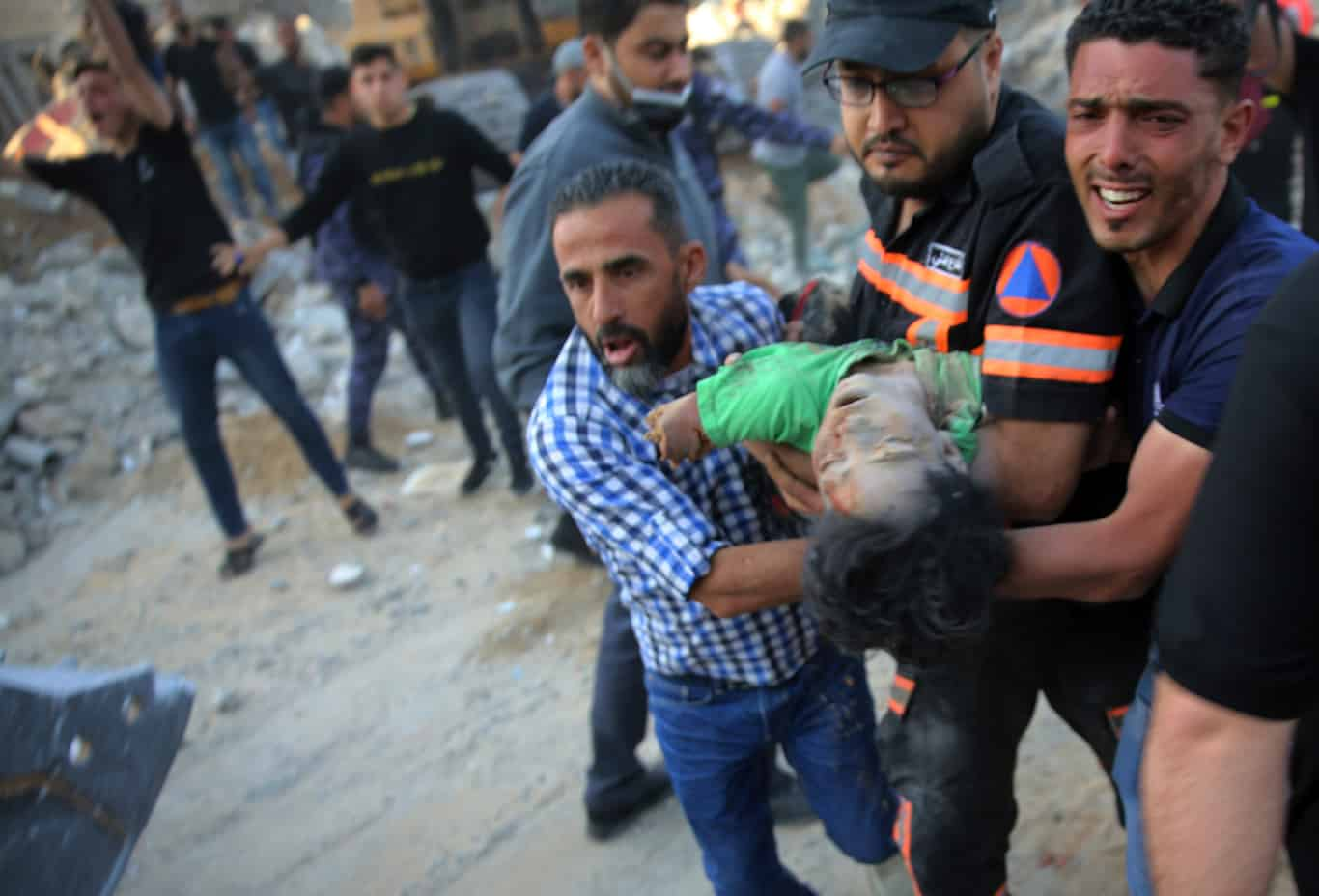 Palestinians carry the body of a child found in the rubble home destroyed by precision Israeli airstrikes in Gaza